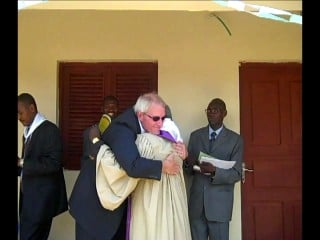 Pastor Mike Solberg hugging Angolan clergyman.