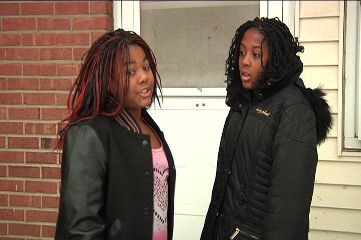Dellell Thomas (left) talks with her sister outside her home.