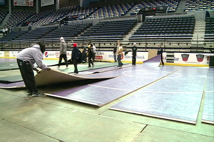 Workers set up mats for the IKWF Tournament